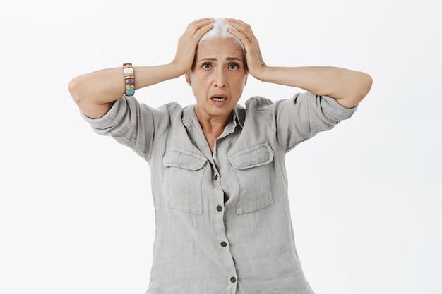 Bezorgde en bezorgde senior vrouw die in paniek raakt, haar hoofd vastpakt en er bedroefd uitziet