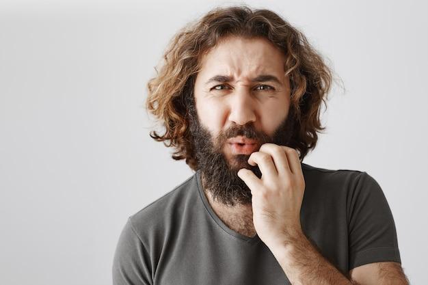 Bezorgde en gefrustreerde man die fronsend iets pijnlijks zag