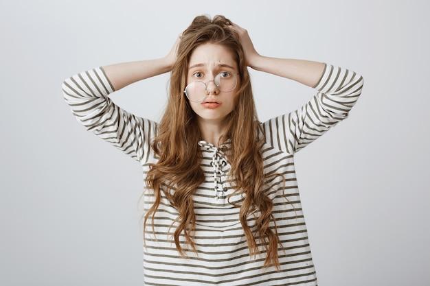 Bezorgde en gestreste vrouw met scheve glazen in paniek, raakte in de problemen