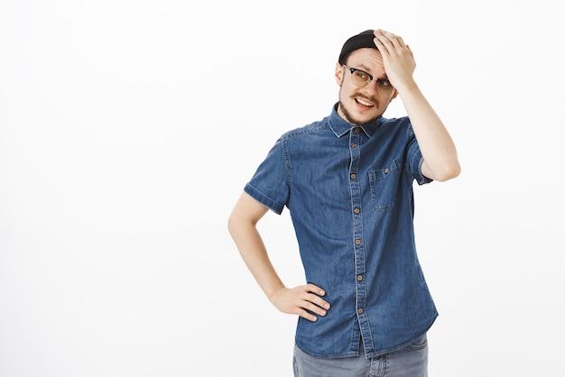 Bezorgde en onrustige jonge mannelijke ondernemer probeert een oplossing te vinden voor problemen met hand op voorhoofd naar links draaien met gehoorde en uitgeputte uitdrukking staande met arm op taille over grijze muur