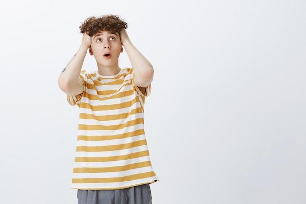 Bezorgde en onrustige tienerjongen die tegen de witte muur poseert