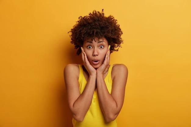 Bezorgde gealarmeerde afro-amerikaanse vrouw met krullend haar grijpt gezicht, staat geschokt en angstig, is getuige van een vreselijk ongeluk, staart naar iets slechts, hoort eng nieuws, draagt felgele kleding
