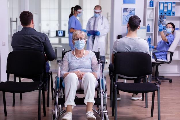 Bezorgde gehandicapte oude vrouw die in een rolstoel zit in de wachtruimte van het ziekenhuis voor doktersonderzoek en naar de camera kijkt