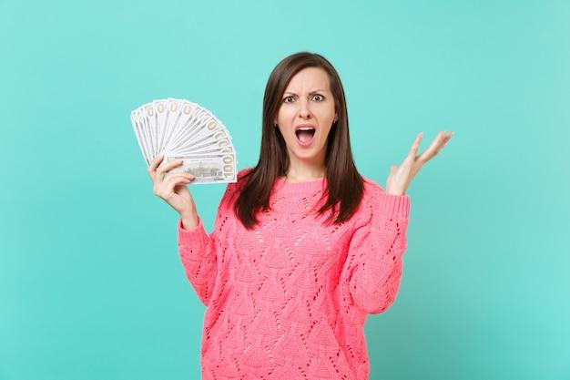 Bezorgde geïrriteerde jonge vrouw in gebreide roze trui die handen verspreidt, houdt veel dollarbankbiljetten vast, contant geld geïsoleerd op blauwe muurachtergrond. mensen levensstijl concept. bespotten kopie ruimte.