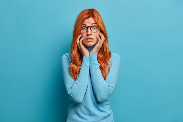 Bezorgde geschokte roodharige jonge vrouw houdt de handen op de wangen en staart verrassend opgewonden door onverwacht nieuws gekleed in vrijetijdskleding.