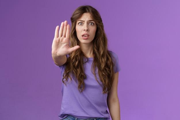 Bezorgde geschokte vrouw met krullend haar hijgend staren camera angstig trekken hand stopbord smeken einde pro...