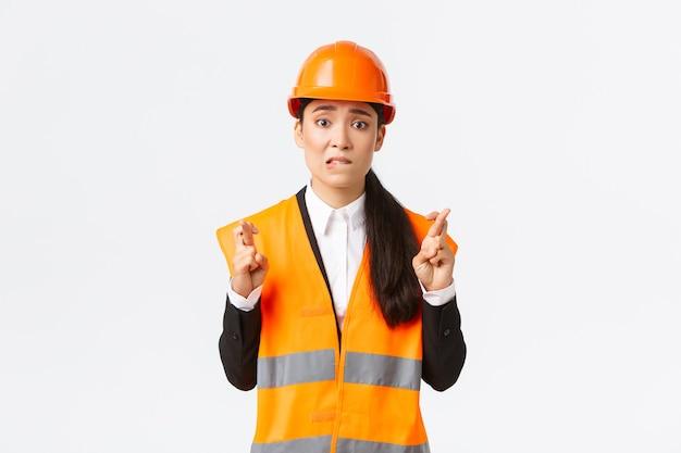 Bezorgde hoopvolle aziatische vrouwelijke architect die zich nerveus voelt terwijl hij wacht op inspectieresultaten in het bouwgebied, veiligheidshelm draagt, vingers gekruist veel geluk, hoop dat alles goed komt