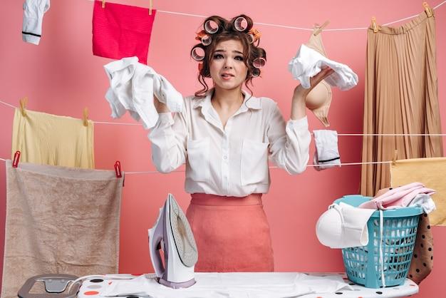 Bezorgde huisvrouw die kleren strijkt