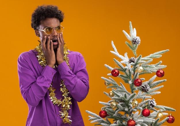 Bezorgde jonge afro-amerikaanse man met bril met klatergoud slinger om nek staande in de buurt van versierde kerstboom op oranje achtergrond