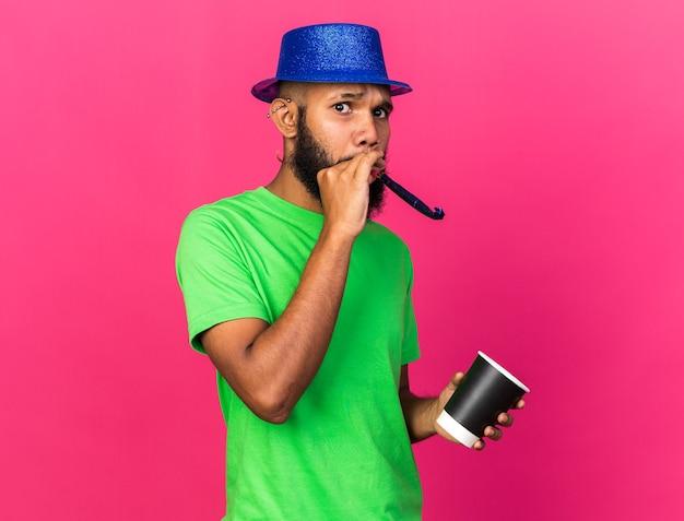 Bezorgde jonge afro-amerikaanse man met een feestmuts die een feestfluitje blaast met een kopje koffie geïsoleerd op een roze muur