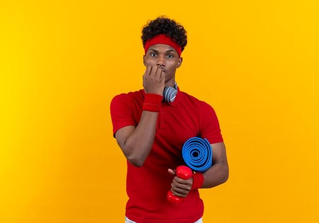 Bezorgde jonge afro-amerikaanse sportieve man met hoofdband en polsbandje met koptelefoon houden yogamat en bijt nagels geïsoleerd op gele achtergrond