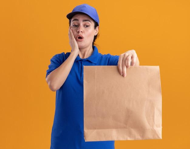 Bezorgde jonge bezorger in uniform en pet die een papieren pakket uitrekt en ernaar kijkt terwijl ze de hand op het gezicht houdt geïsoleerd op de oranje muur