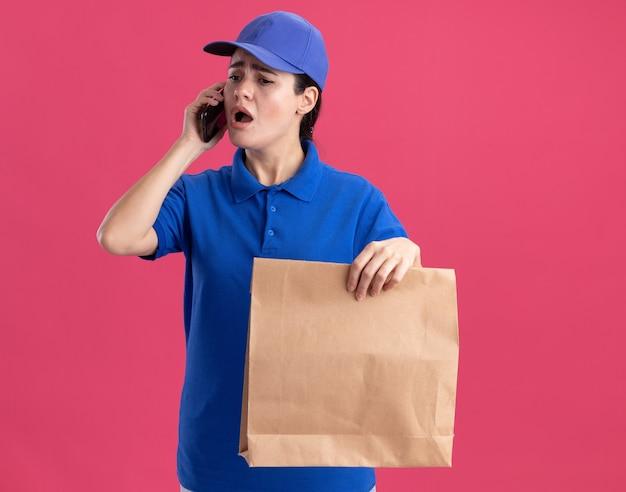Bezorgde jonge bezorger in uniform en pet met papieren pakket die aan de telefoon praat en naar beneden kijkt geïsoleerd op roze muur met kopieerruimte