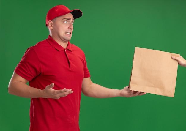 Bezorgde jonge bezorger met uniform en pet die papieren voedselpakket geeft aan klant geïsoleerd op groene muur