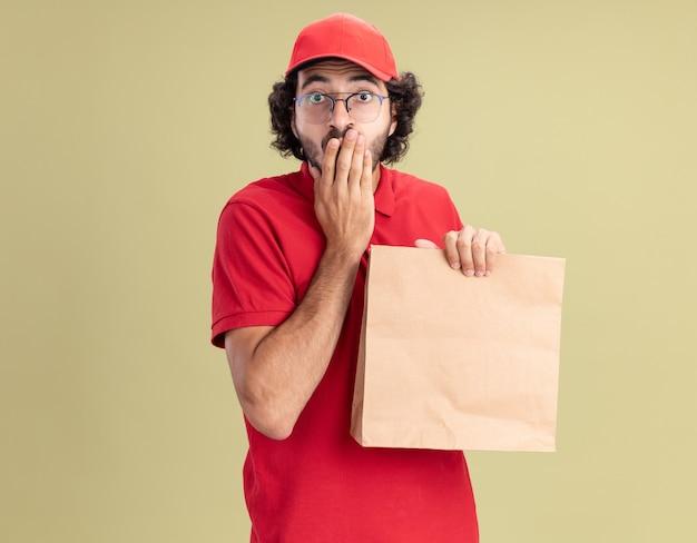 Bezorgde jonge blanke bezorger in rood uniform en pet met een bril met papieren pakket die de hand op de mond houdt geïsoleerd op olijfgroene muur met kopieerruimte