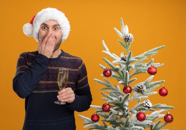 Bezorgde jonge blanke man met kerstmuts staande in de buurt van versierde kerstboom met glas champagne hand op mond houden geïsoleerd op oranje muur