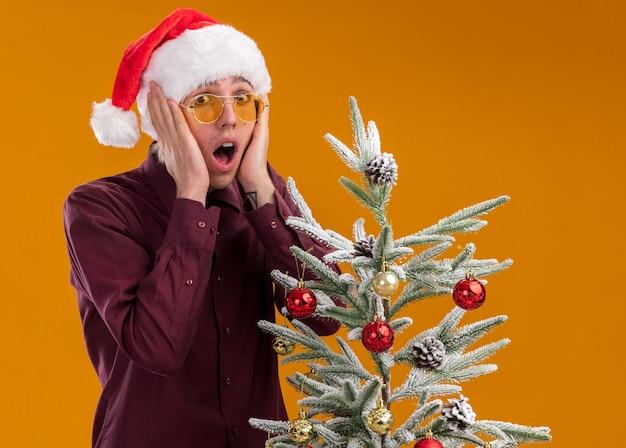 Bezorgde jonge blonde man met kerstmuts en bril staan in de buurt van versierde kerstboom handen houden op gezicht geïsoleerd op oranje muur