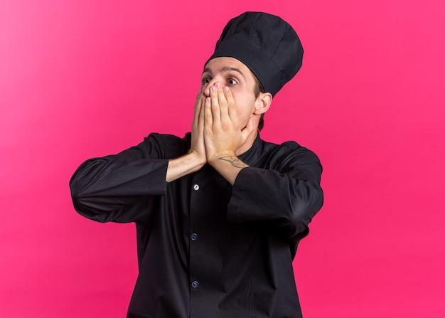 Bezorgde jonge blonde mannelijke kok in uniform van de chef-kok en dop die de mond bedekt met handen die naar de zijkant kijken geïsoleerd op roze muur