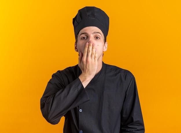 Bezorgde jonge blonde mannelijke kok in uniform van de chef-kok en pet kijkend naar camera die mond bedekt met hand geïsoleerd op oranje muur