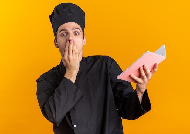 Bezorgde jonge blonde mannelijke kok in uniform van de chef-kok en pet met notitieblok kijkend naar camera met hand op mond geïsoleerd op oranje muur