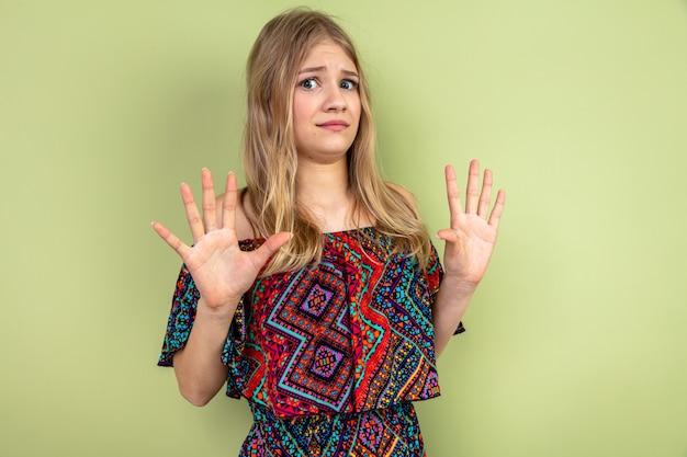 Bezorgde jonge blonde slavische vrouw die zich met opgeheven handen bevindt