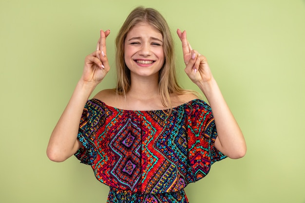 Bezorgde jonge blonde vrouw die haar vingers kruist