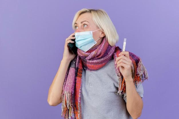 Bezorgde jonge blonde zieke slavische vrouw die medische masker en sjaal draagt