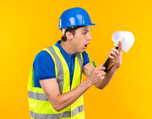 Bezorgde jonge bouwer man in uniform houden en kijken naar klembord geïsoleerd op gele muur