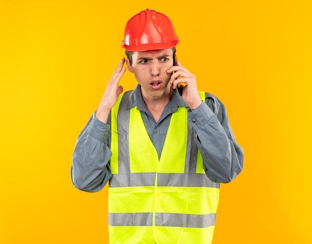 Bezorgde jonge bouwer man in uniform spreekt op telefoon geïsoleerd op gele muur