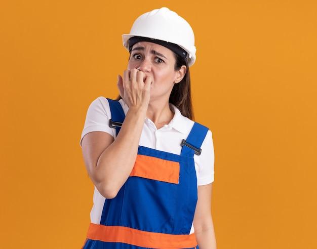 Bezorgde jonge bouwvrouw in uniform bijt nagels geïsoleerd op oranje muur