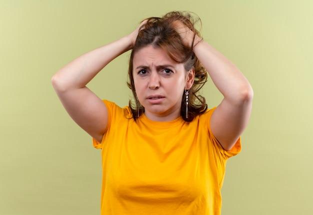 Bezorgde jonge casual vrouw met handen op het hoofd op geïsoleerde groene ruimte