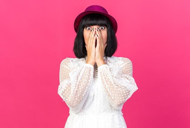 Bezorgde jonge feestvrouw met een feesthoed die naar de voorkant kijkt en de handen op de mond houdt, geïsoleerd op een roze muur