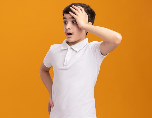 Bezorgde jonge jongen die zijn hand op zijn hoofd houdt en een andere op zijn middel houdt, kijkend naar de zijkant geïsoleerd op een oranje muur