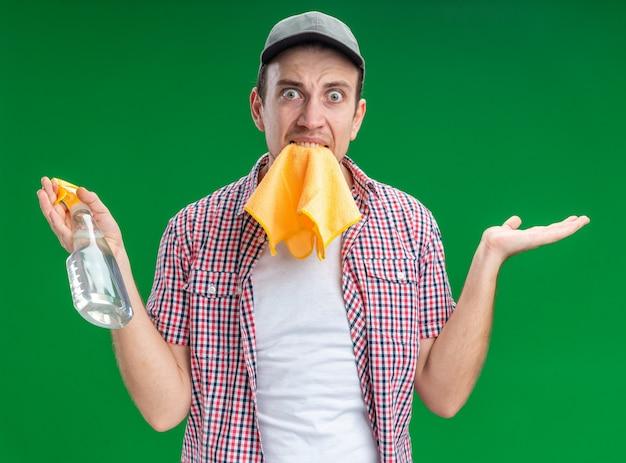 Bezorgde jonge kerel die een pet draagt met een schoonmaakmiddel dat de hand verspreidt die op een groene muur wordt geïsoleerd