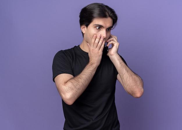 Bezorgde jonge knappe man met een zwart t-shirt spreekt op telefoon bedekte mond met hand geïsoleerd op paarse muur