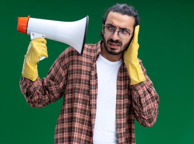 Bezorgde jonge knappe schoonmaakster met t-shirt en handschoenen die met luidspreker bedekt oor vasthoudt en kijkt met hand geïsoleerd op groene muur