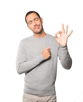 Bezorgde jonge man die twijfelt en een gebaar van goedkeuring maakt