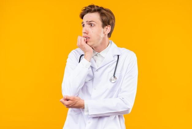 Bezorgde jonge mannelijke arts die medisch gewaad draagt met stethoscoop bijt nagels geïsoleerd op oranje muur