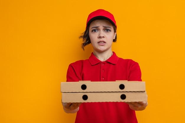 Bezorgde jonge mooie bezorger die pizzadozen vasthoudt