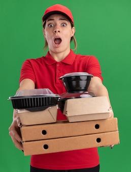 Bezorgde jonge mooie bezorger in uniform houdt papieren voedselpakketten en containers op pizzadozen die op groene muur worden geïsoleerd