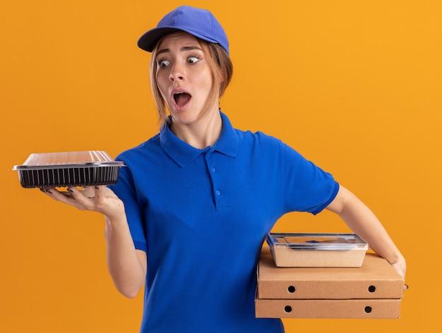 Bezorgde jonge mooie bezorger in uniform houdt papieren voedselpakketten en containers op pizzadozen geïsoleerd op een oranje muur