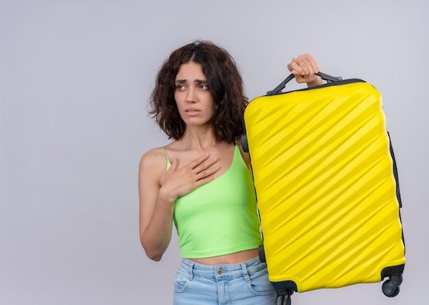 Bezorgde jonge mooie reizigersvrouw die koffer opheft en hand op borst op geïsoleerde witte muur met exemplaarruimte zet