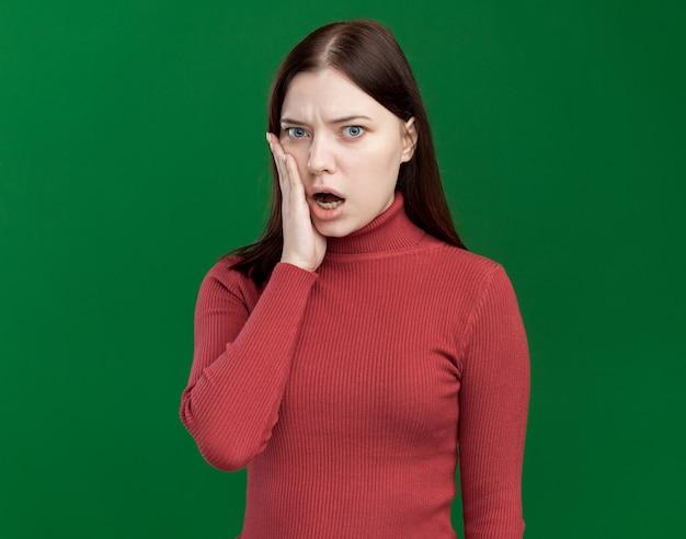 Bezorgde jonge mooie vrouw die naar de voorkant kijkt en de hand op het gezicht houdt geïsoleerd op een groene muur met kopieerruimte