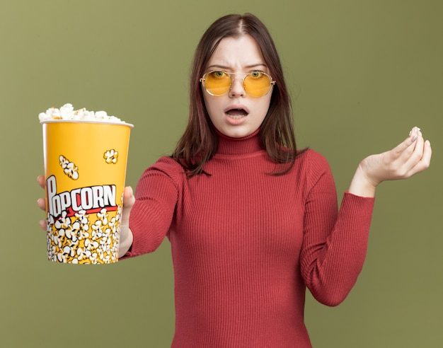 Bezorgde jonge mooie vrouw met emmer popcorns