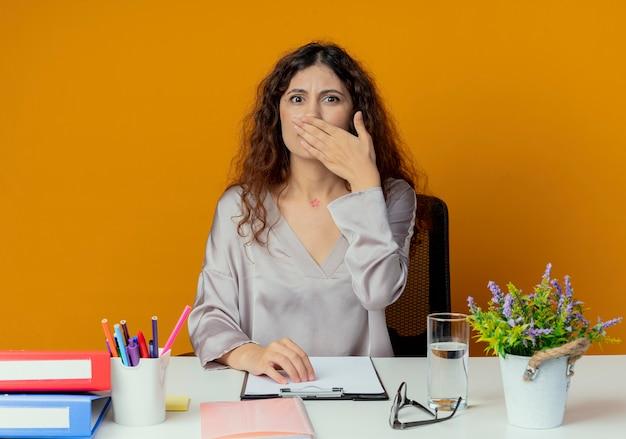 Bezorgde jonge, mooie vrouwelijke kantoormedewerker die aan het bureau zit