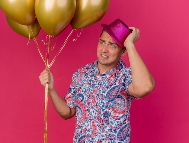 Bezorgde jonge partij kerel kijken naar kant dragen roze hoed met ballonnen en pakte hoed geïsoleerd op roze achtergrond