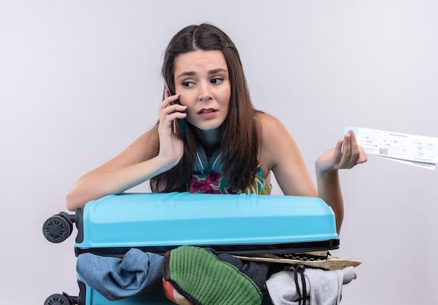 Bezorgde jonge reizigersvrouw die op telefoonkaartjes op geïsoleerde witte muur spreken