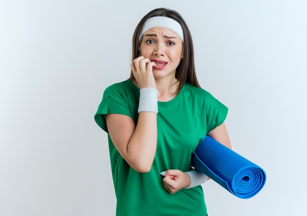 Bezorgde jonge sportieve vrouw die hoofdband en polsbandjes draagt die de mat bijtende vingers van de holdingsyoga kijken