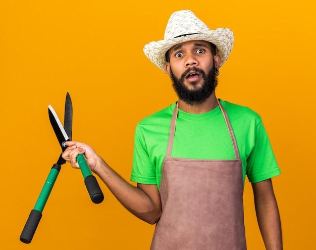 Bezorgde jonge tuinman afro-amerikaanse man met een tuinhoed met tondeuses geïsoleerd op een oranje muur