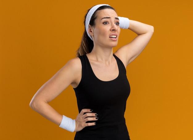 Bezorgde jonge, vrij sportieve vrouw met hoofdband en polsbandjes die de handen op de taille en op het hoofd houden en naar de zijkant kijken